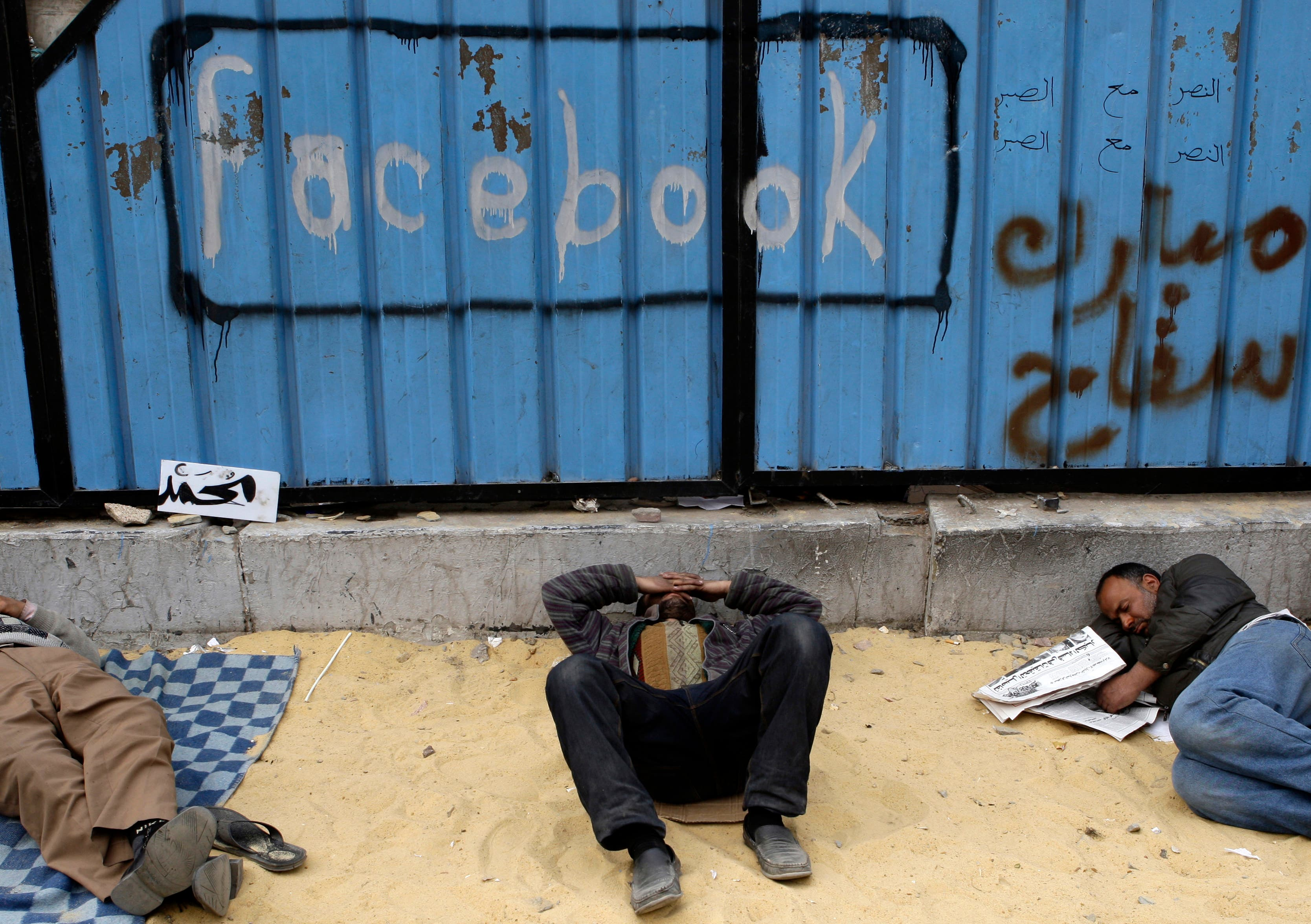 Facebook_BODY1: Opposition supporters rest near graffiti referring to Facebook in Tahrir Square in Cairo on February 5, 2011. (File photo: Reuters)