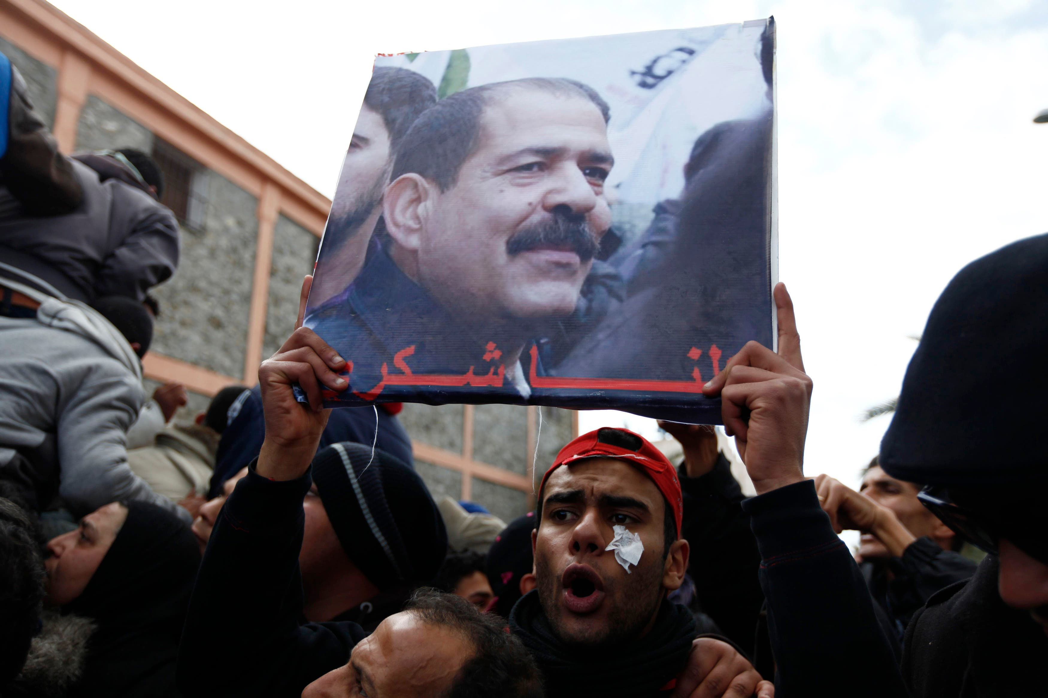 A placard with an image of the late secular opposition leader Chokri Belaid is displayed during his funeral procession in the Jebel Jelloud district in Tunis Feb. 8, 2013. (Reuters)