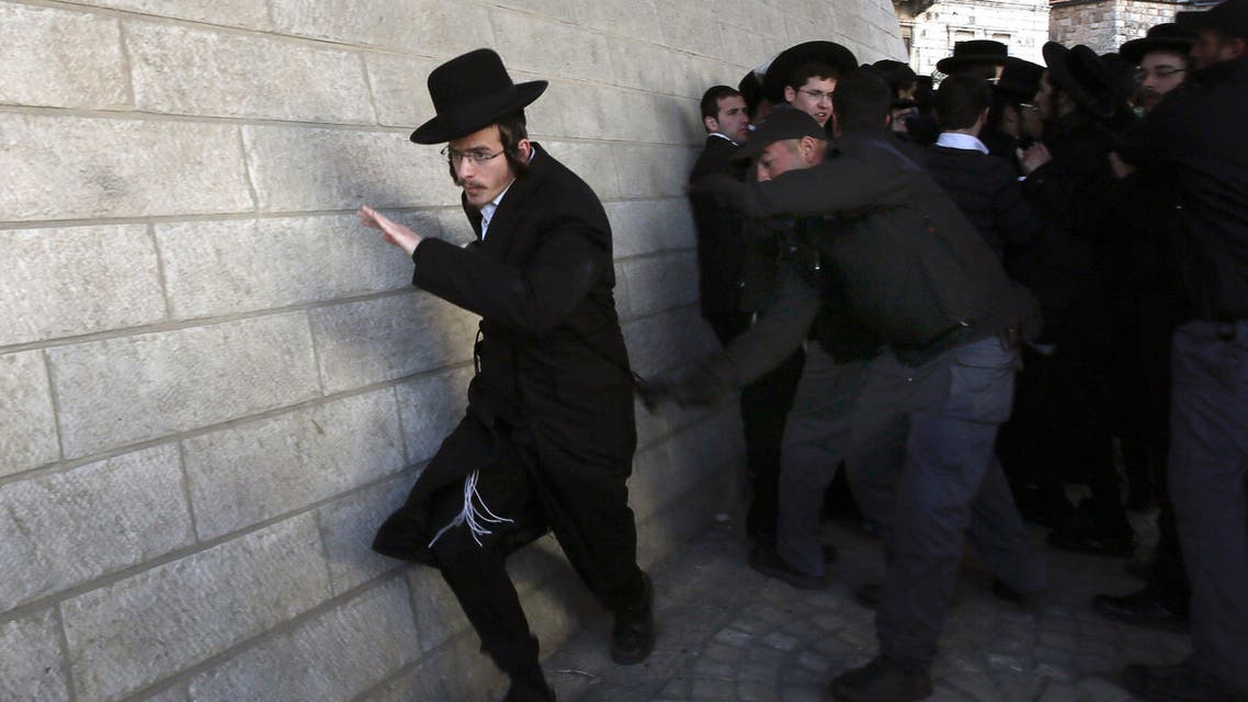 Israeli policemen scuffle with ultra-Orthodox Jews during a protest against their young men being called up for military service on Feb. 6, 2014 in Jerusalem. (AFP)
