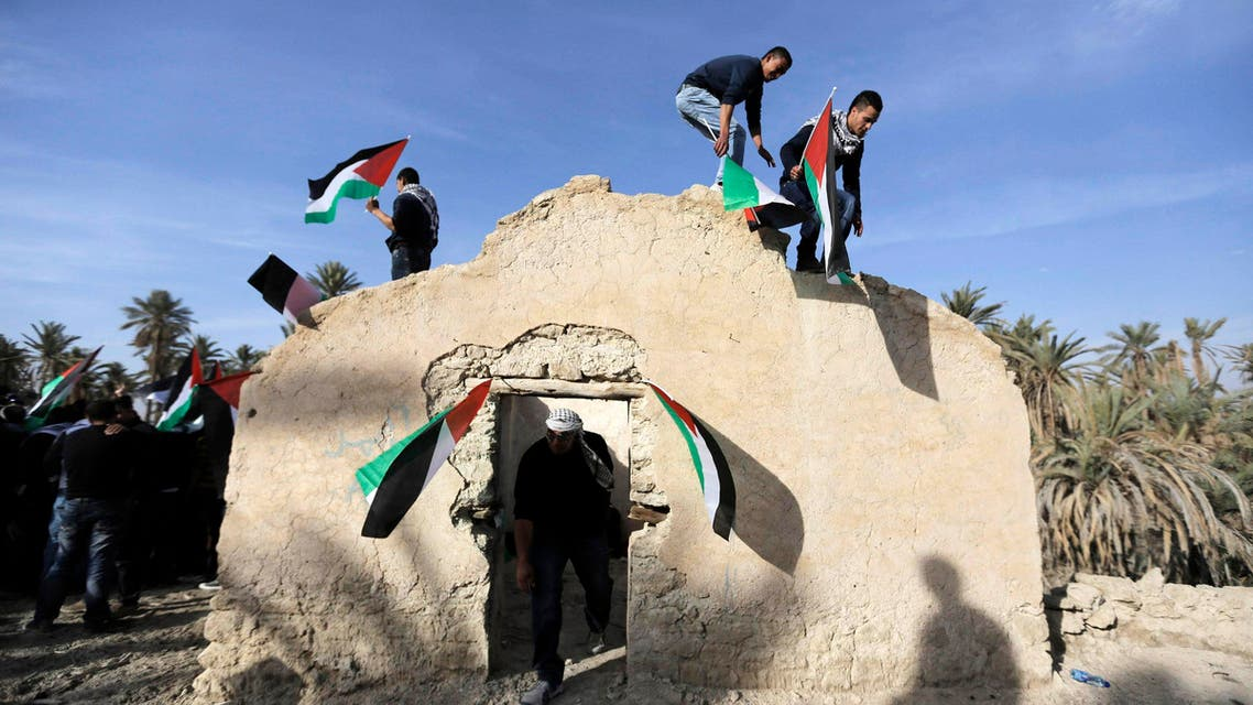 Palestinian and foreign activists hold Palestinian flags as they climb on top of a structure in an old village known as Ein Hajla, in the Jordan Valley near the West Bank city of Jericho Jan. 31, 2014. (Reuters)
