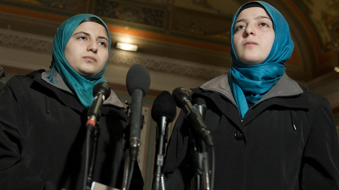 Sisters Heba Sawan (L) and Amineh Sawan, survivors of the August 2013 chemical weapons attack in Moadamiya, Syria, speak during a press conference at the US Capitol in Washington, DC, Feb. 6, 2014. (AFP)