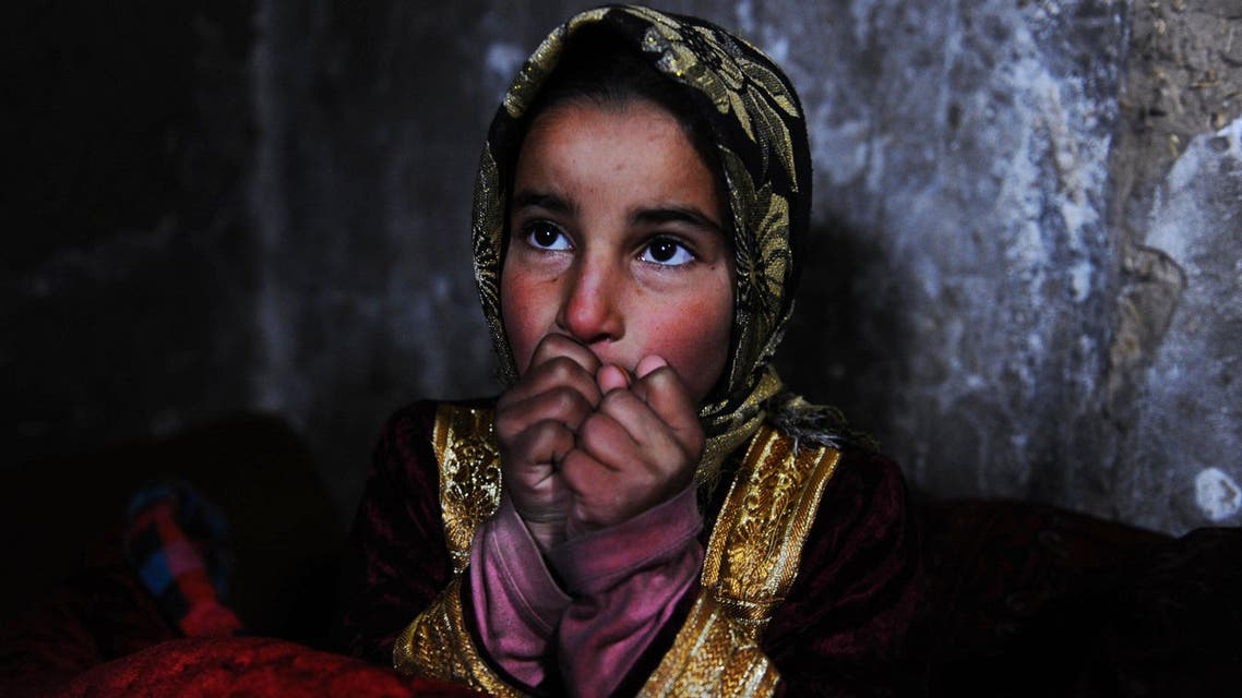 """An Afghan child warms herself near a traditional """"sandali"""" stove at her family's home in Herat on Feb. 7, 2014. (AFP)"""