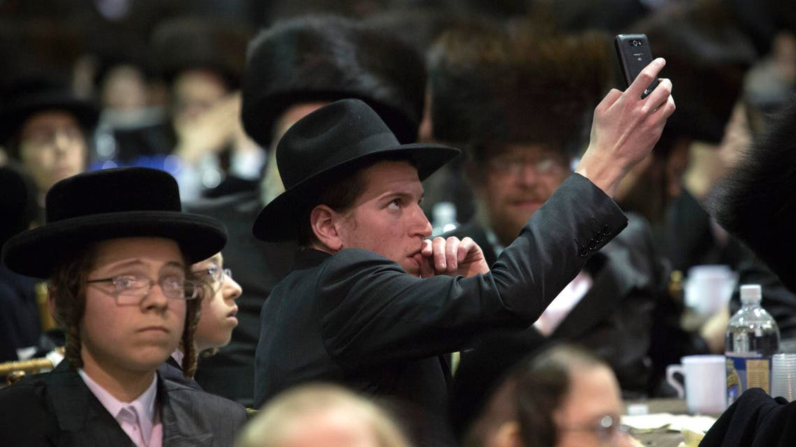 A man takes photos using his phone at a mass gathering of Satmar Hasidic Jews in New York Nov. 24, 2013. (Reuters)