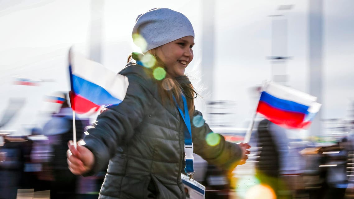 A girl wearing a fan entrance ticket runs with Russian national flags at the Olympic Park during the Sochi 2014 Winter Olympics Games February 9, 2014.