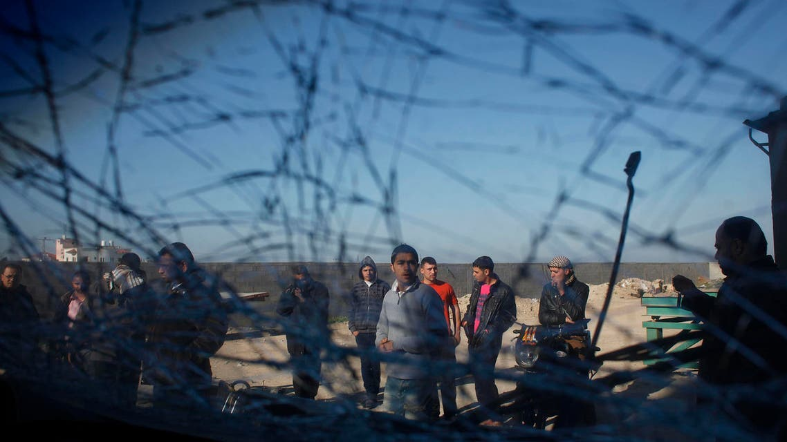 Palestinians are seen through a damaged car window as they look at the scene of an Israeli air strike in the centre of the Gaza Strip February 9, 2014. reut