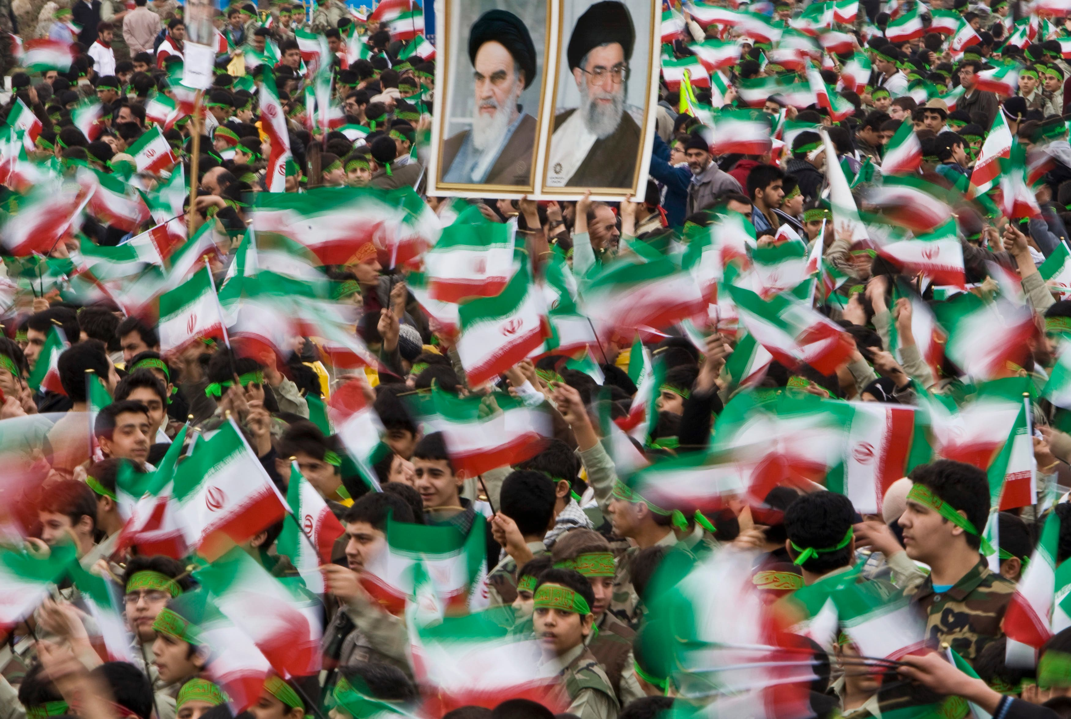 Students wave Iran's national flag as others hold pictures of Iran's Supreme Leader Ali Khamenei (R) and Iran's late leader Ruhollah Khomeini during a ceremony to mark the anniversary of Iran's 1979 Islamic Revolution on February 10, 2009. (Reuters)