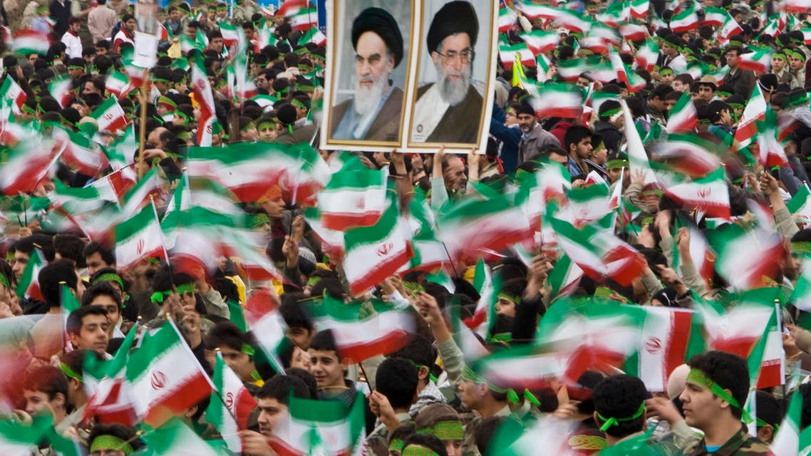 Students wave Iran's national flag as others hold pictures of Iran's Supreme Leader Ayatollah Ali Khamenei (R) and Iran's late leader Ayatollah Ruhollah Khomeini during a ceremony to mark the anniversary of Iran's 1979 Islamic Revolution, in Tehran's Azadi (Freedom) Square February 10, 2009 reut