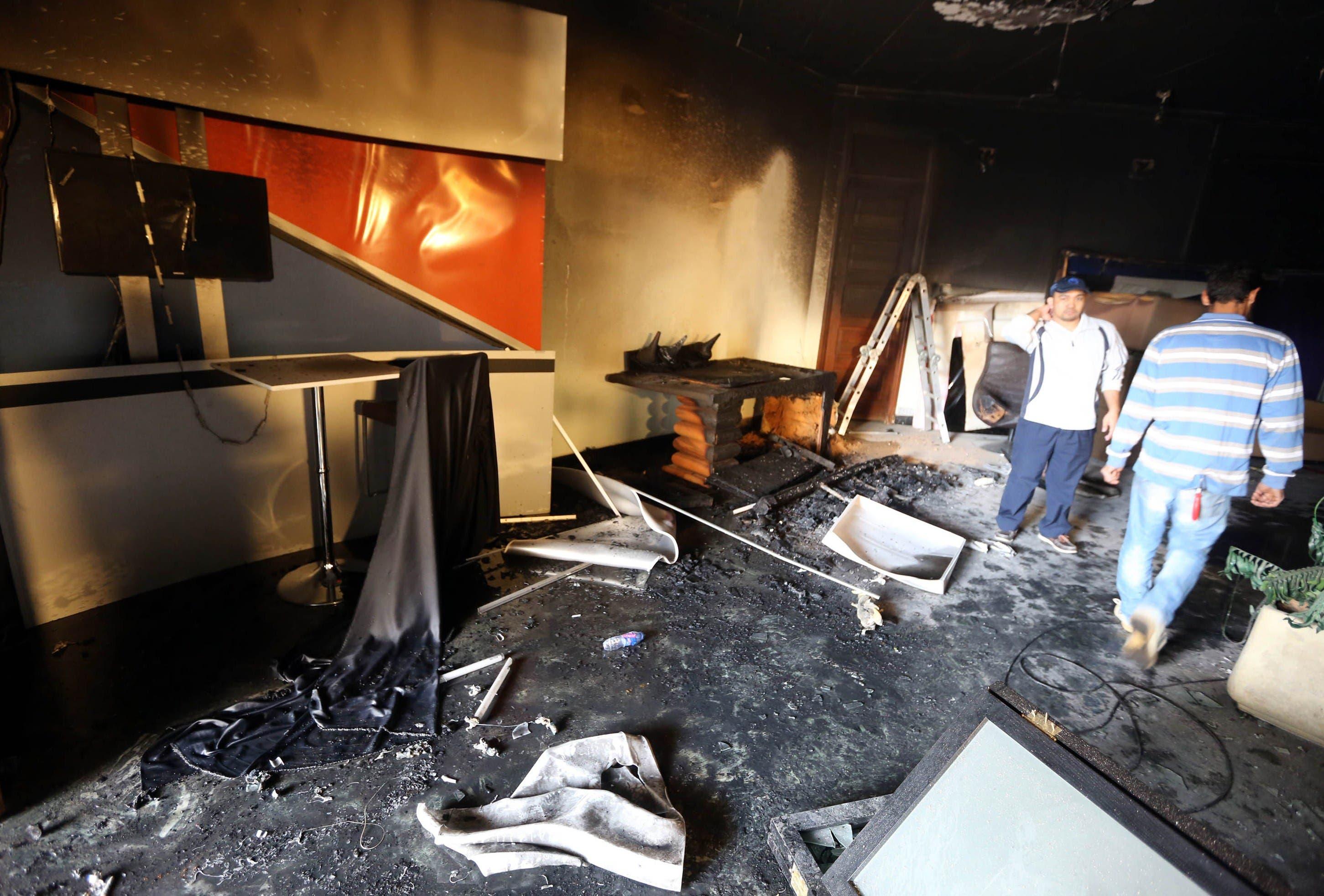 Men inspect a damaged room at the Alassema TV station. (AFP)
