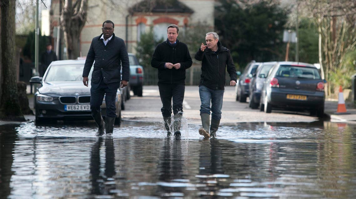 Britain's Prime Minister David Cameron (C) speaks with resident Ray Connerlley (R) and Kwasi Kwarteng, the MP for Spelthorne, as they walk through flood water in Guildford Street in Staines-upon-Thames, southwest of London February 11, 2014. reut