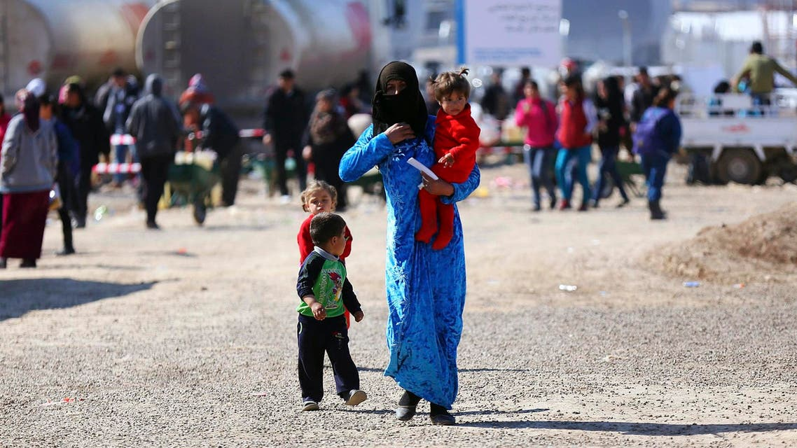 A Syrian refugee woman walks to receive her share of humanitarian aid in Quru Gusik refugee camp on the outskirts of Arbil, in Iraq's Kurdistan region, Feb. 10, 2014. (Reuters)