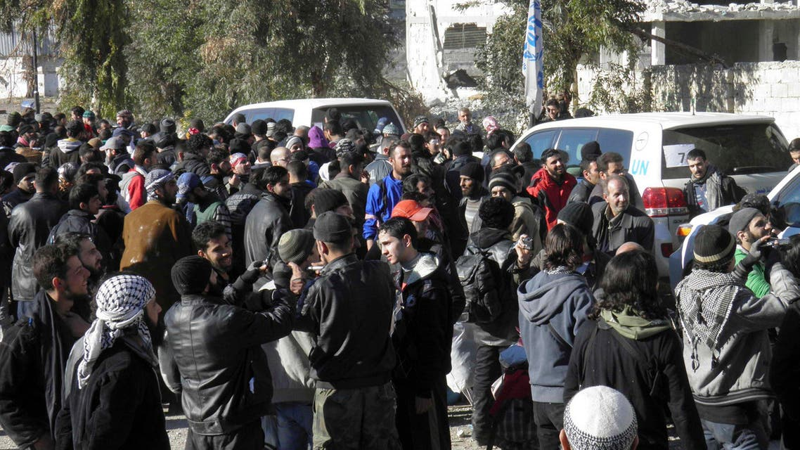 Civilians gathered near Syrian Arab Red Crescent and United Nations vehicles wait to be evacuated from a besieged area of Homs, Feb. 12, 2014. (Reuters)