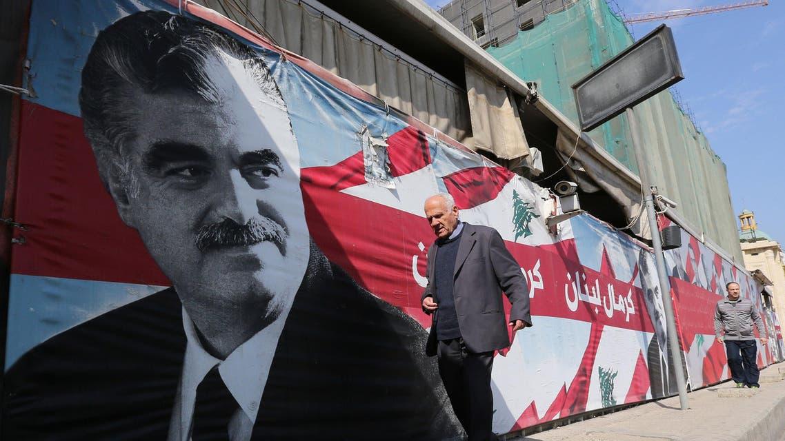 A man walks past a portrait of slain Lebanese premier Rafiq Hariri on the ninth anniversary of his death on February 14, 2014. AFP