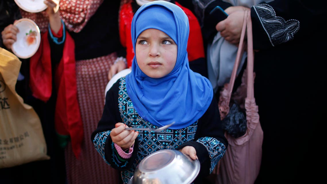 A Palestinian girl makes noise with a metal bowl and spoon as she takes part in a rally to show solidarity with Palestinian refugees in Syria's main refugee camp Yarmouk, in Gaza City January 16, 2014. Reuters