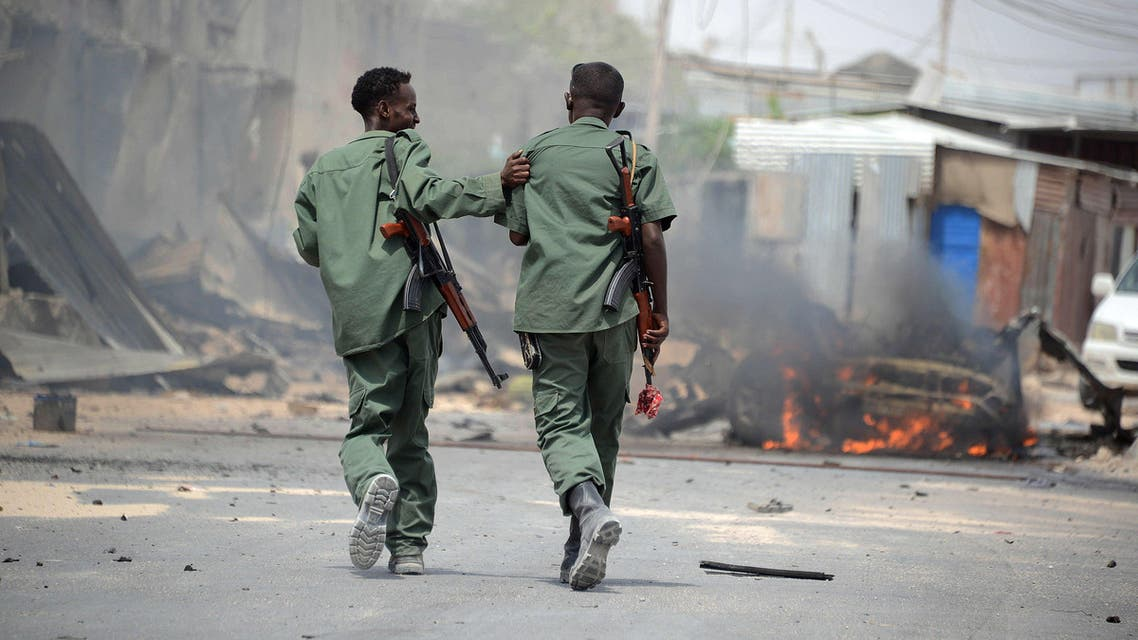 Two Somali soldiers walk past a building burning following a car bomb explosion on February 13, 2014 afp