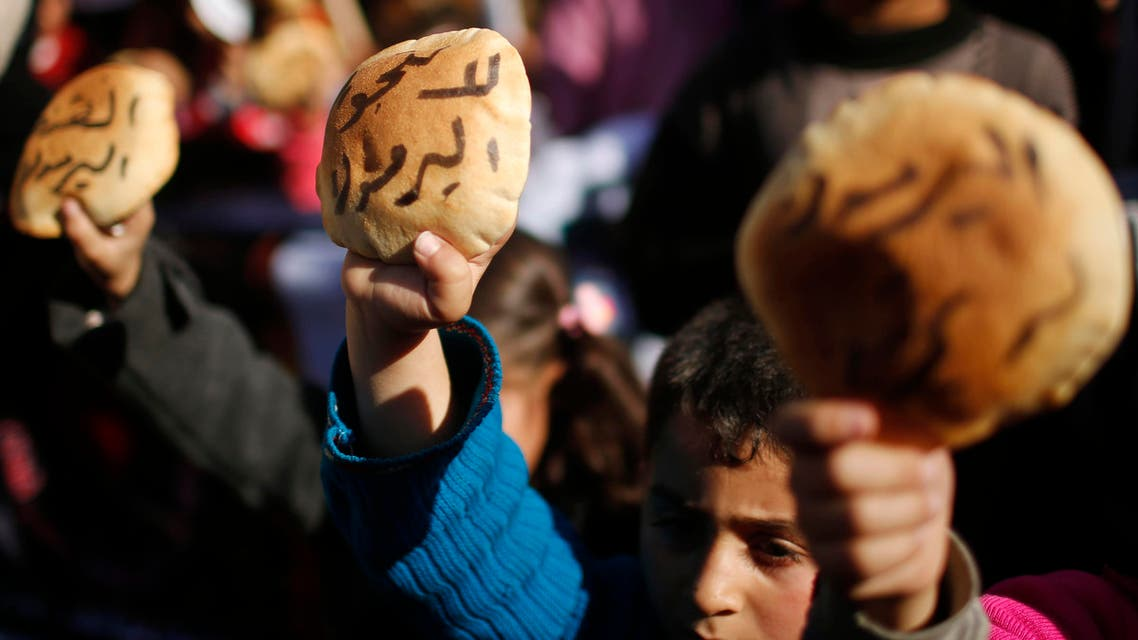 Palestinian children hold bread as they take part in a rally to show solidarity with Palestinian refugees in Syria's main refugee camp Yarmouk, in Gaza City January 16, 2014.  reuters