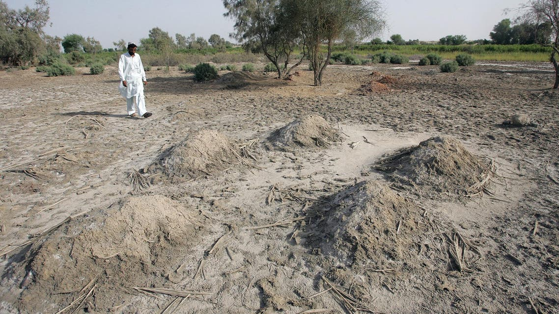 """A Pakistani villager walks past nameless graves in burial grounds reserved for """"karo kari"""" or honour killing near Daharki, 550 km (340 miles) from Karachi. Literally a """"black woman"""", a """"kari"""" is a woman accused of having sex outside of marriage, while """"karo"""" is the male version. (File: Reuters)"""