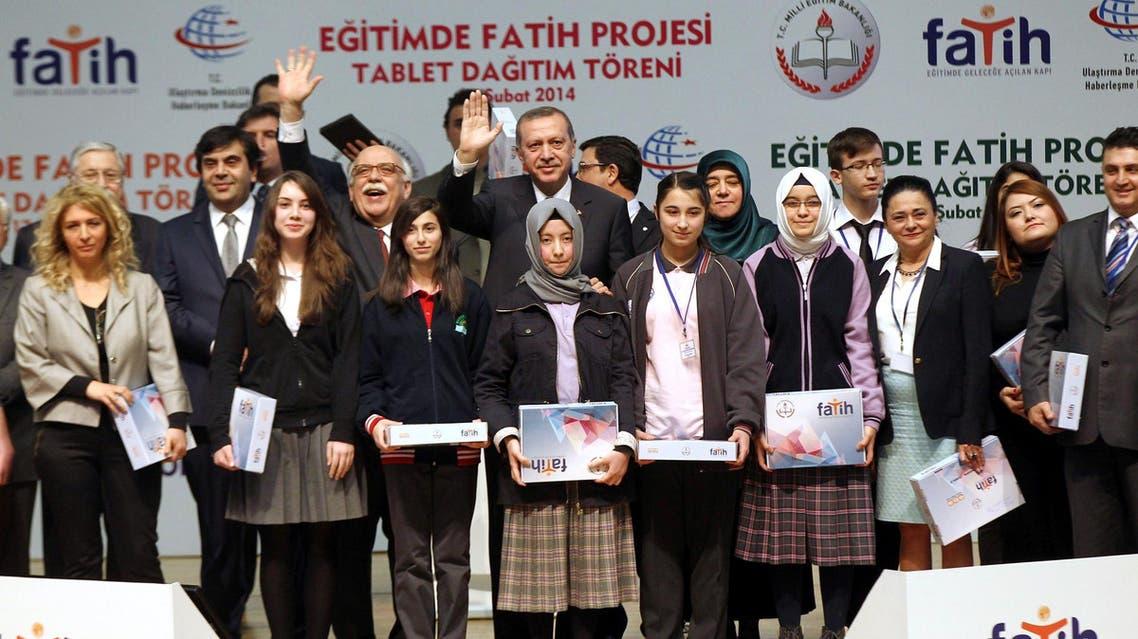 اردوغان أثناء تسليمه أجهزة كمبيوتر لوحية لعدد من طلاب المدارس