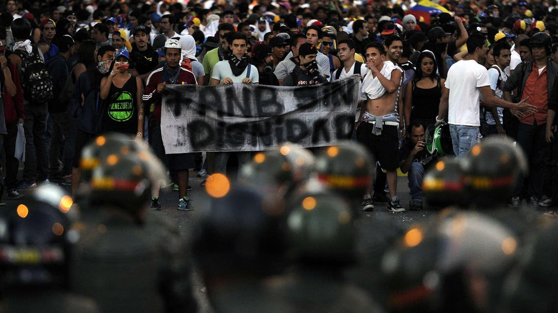 "Anti-government students staging a protest hold a banner reading ""FANB (National Bolivarian Armed Forces) without dignity"" in front of members of the National Guard in Caracas on February 16, 2014. afp"