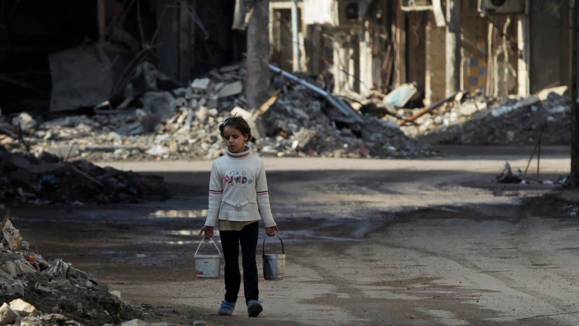 طفلة تحمل دلوا من الماء في سوريا