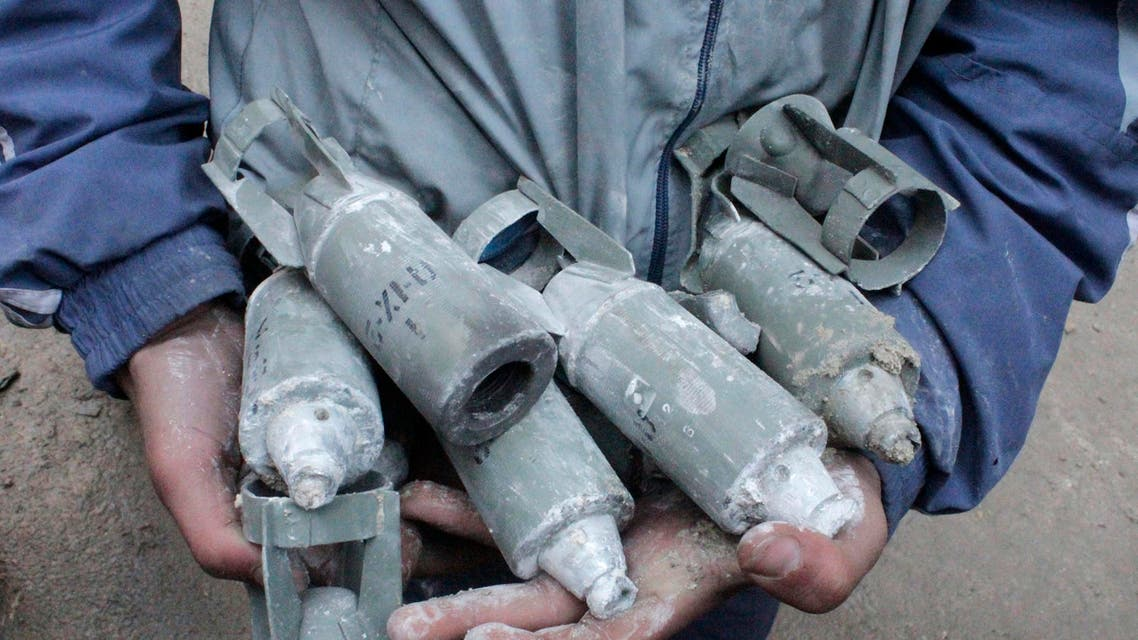 A boy holds unexploded cluster bombs after jet shelling by forces loyal to Syria's President Bashar al-Assad in the al-Meyasar district of Aleppo February 21, 2013. reuters