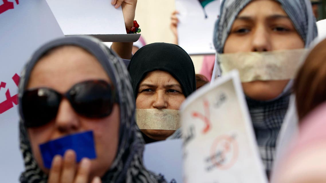 Libyan women with taped mouths take part in a silent march in support of the women who were raped during the recent war in Libya, in Tripoli Nov. 26, 2011. (Reuters)