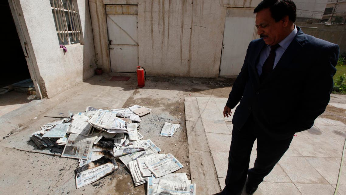 An Iraqi journalist walks past the archive newspapers burned after attack by an armed group at the newspaper's headquarters of Addustour newspaper in Baghdad, April 2, 2013.  (File photo: Reuters)