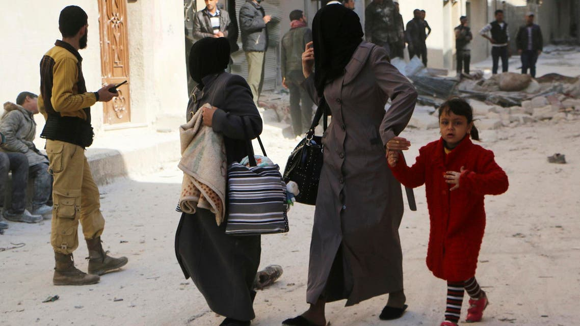 Women walk at a damaged site after what activists said was an air strike by forces loyal to Syria's President Bashar al-Assad in Masaken Hanano in Aleppo Feb.14, 2014. (Reuters)