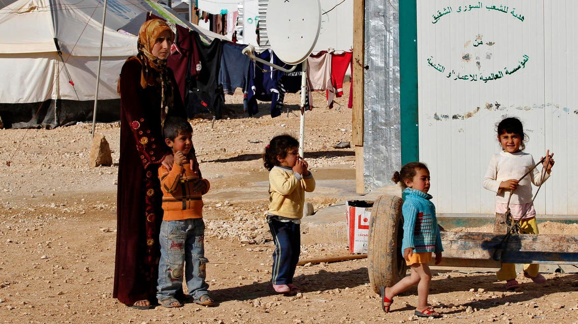 A Syrian refugee woman watches as her children play at the Zaatri refugee camp, in the Jordanian city of Mafraq, near the border with Syria Feb. 18, 2014. (