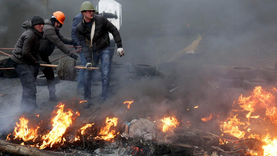 Anti-government protesters reel barbed wire around a barricade during clashes with riot police in the Independence Square in Kiev, Feb. 20, 2014. (Reuters)