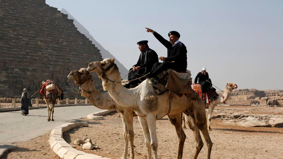 A police officer sitting on a camel talks to workers at the Giza pyramids, south of Cairo, Feb, 20, 2014. (Reuters)