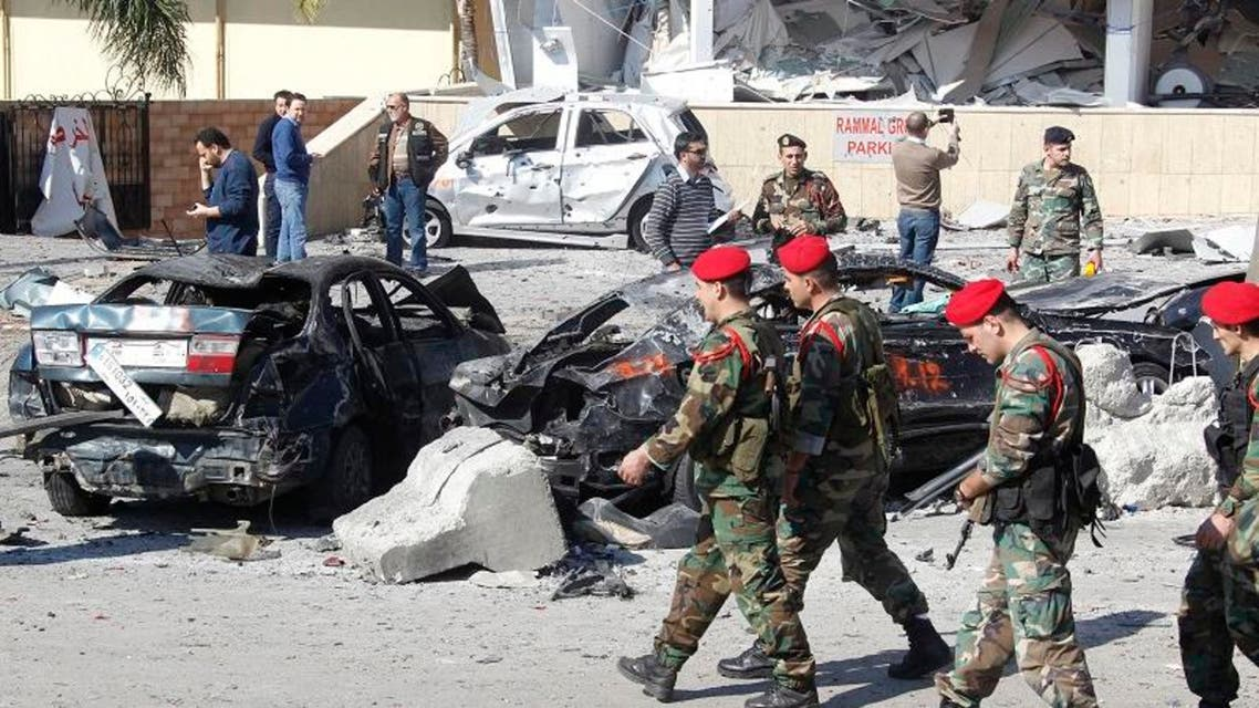Lebanese army soldiers walk past damaged cars at the site of Wednesday's explosion in the southern suburbs of Beirut February 20, 2014.