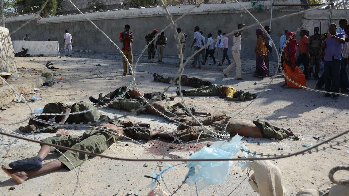People walk past the bodies of seven Al Shebab rebels in front the presidential palace on February 21, 2014 in Mogadishu.