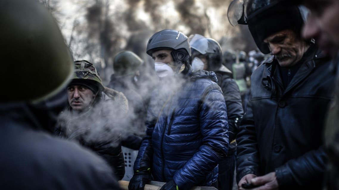 Anti-government demonstrator wearing helmets and masks stand behind their barricade on February 21, 2014 at the Independent square in Kiev. afp