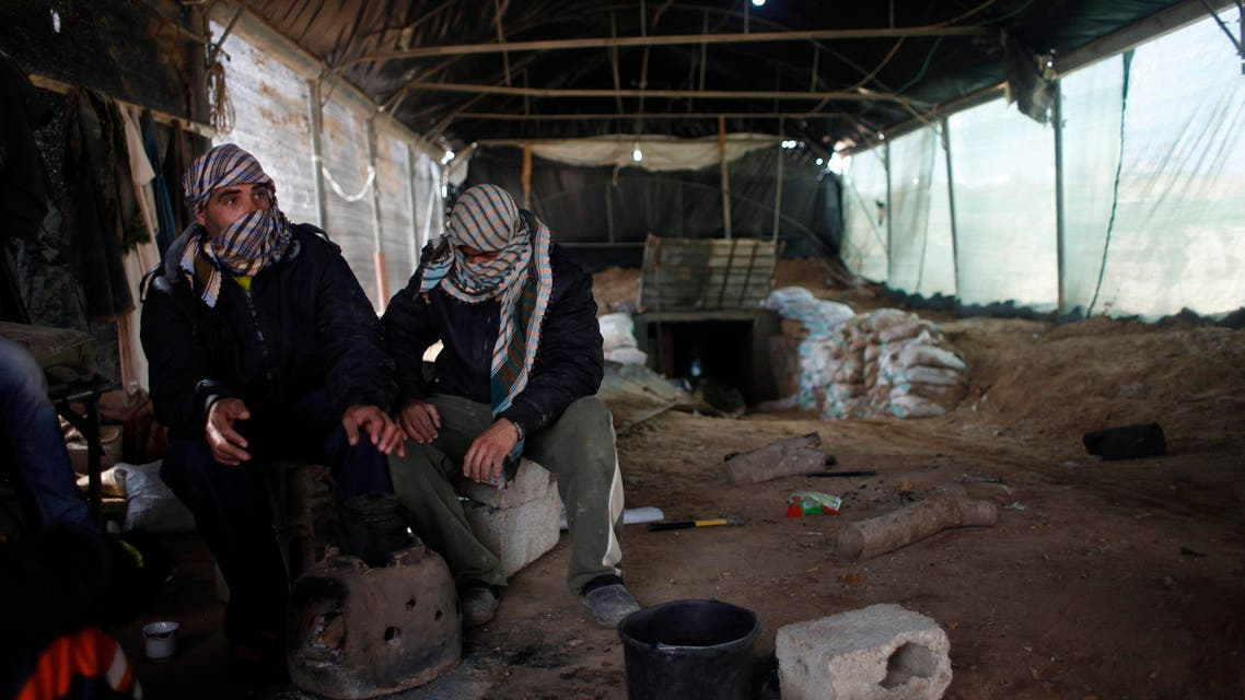 Tunnel workers sit outside a smuggling tunnel on the border between Egypt and the southern Gaza Strip February 17, 2014. (Reuters)