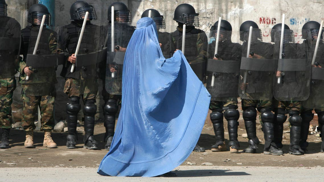 A woman wearing a burqa walks past riot police outside a gathering in Kabul. (File photo: Reuters)