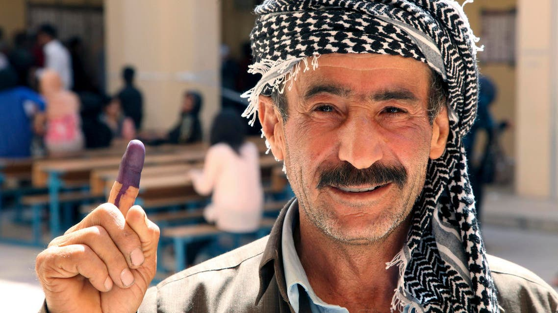An Iraqi Kurdish man shows his ink-stained finger after voting during regional parliamentary elections at a polling station in Arbil