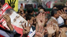 Egypt's Mursi urges 'revolution' from caged dock