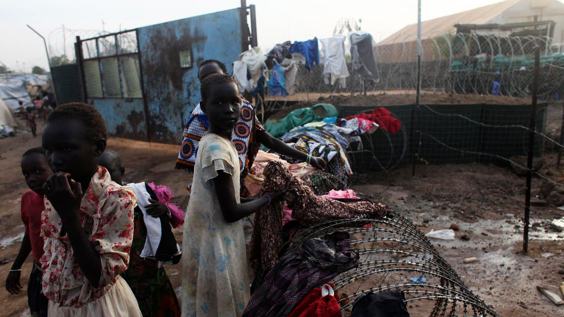 South Sudanese girls displaced by the fighting collect their laundry from a barbed wire in a camp for displaced persons in the UNMISS compound in Tongping in Juba, Feb. 19, 2014. (Reuters)