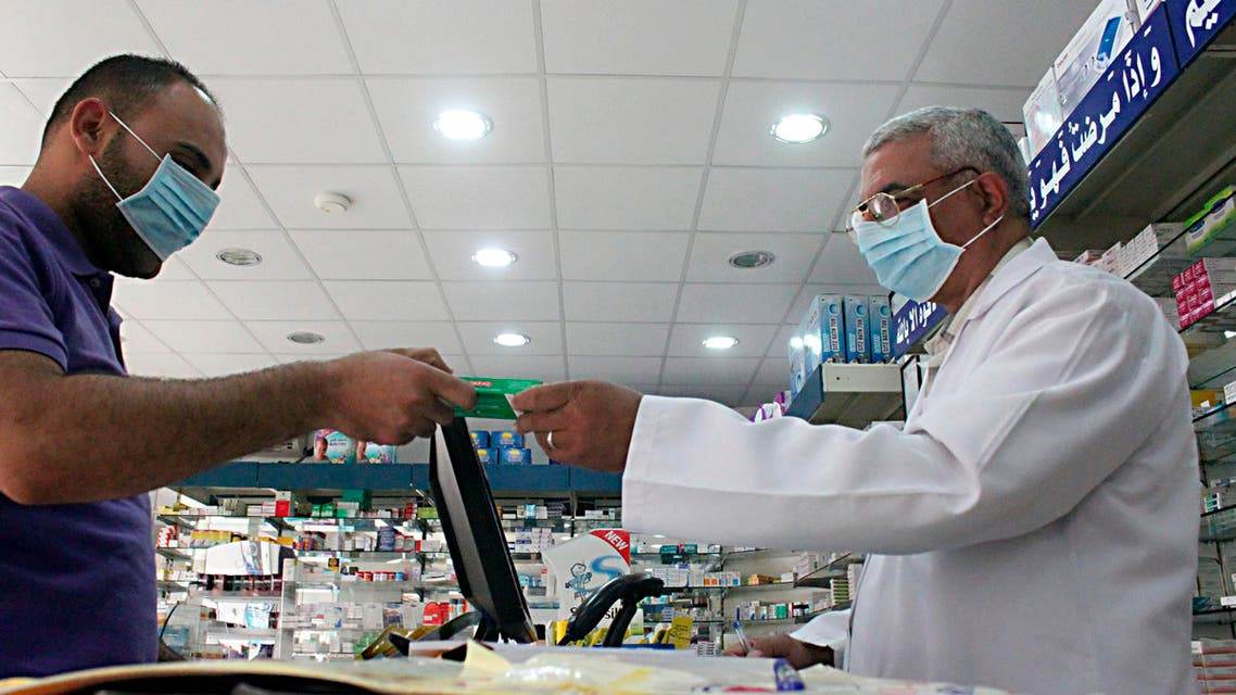 A man, wearing a surgical mask as a precautionary measure against the novel coronavirus, pays for medicine at a hospital pharmacy in Khobar city in Dammam May 21, 2013. reuters