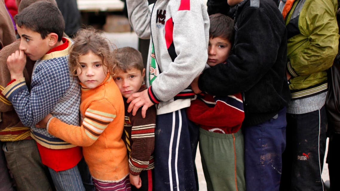 Syrian refugee children queue as they wait to receive aid from Turkish humanitarian agencies at Bab al-Salam refugee camp in Syria near the Turkish border December 22, 2012. reuters