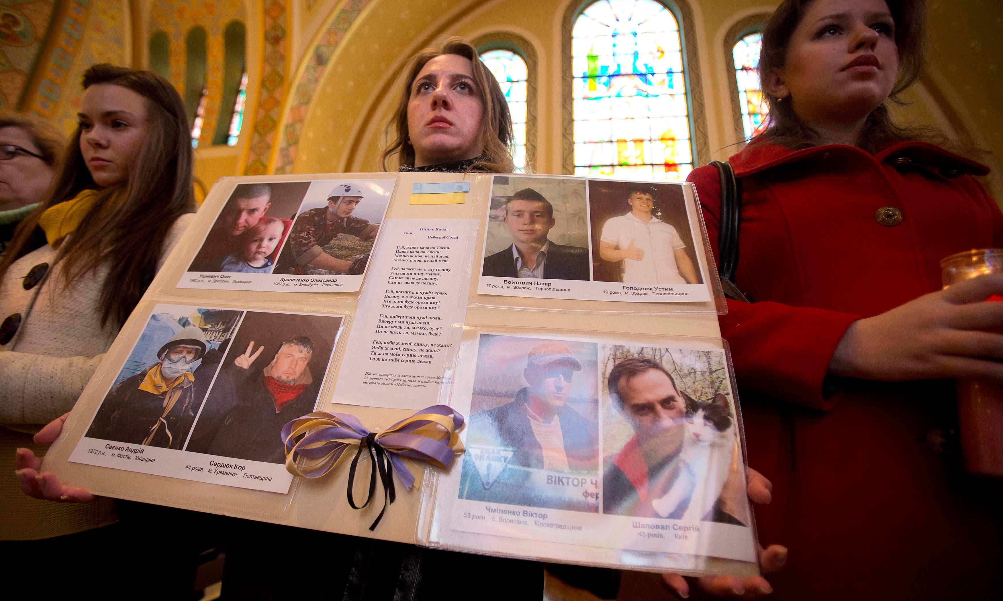 اهالي ضحايا الاشتباكات بين قوات الامن والمعارضين يرفعون صورهم في كنيسة في اوكرانيا