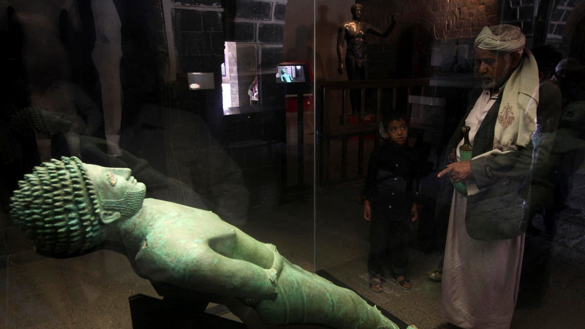 A man looks at an ancient bronze statue of Yemeni King Hawtar Athat, at the National Museum in Sanaa. (File photo Reuters)