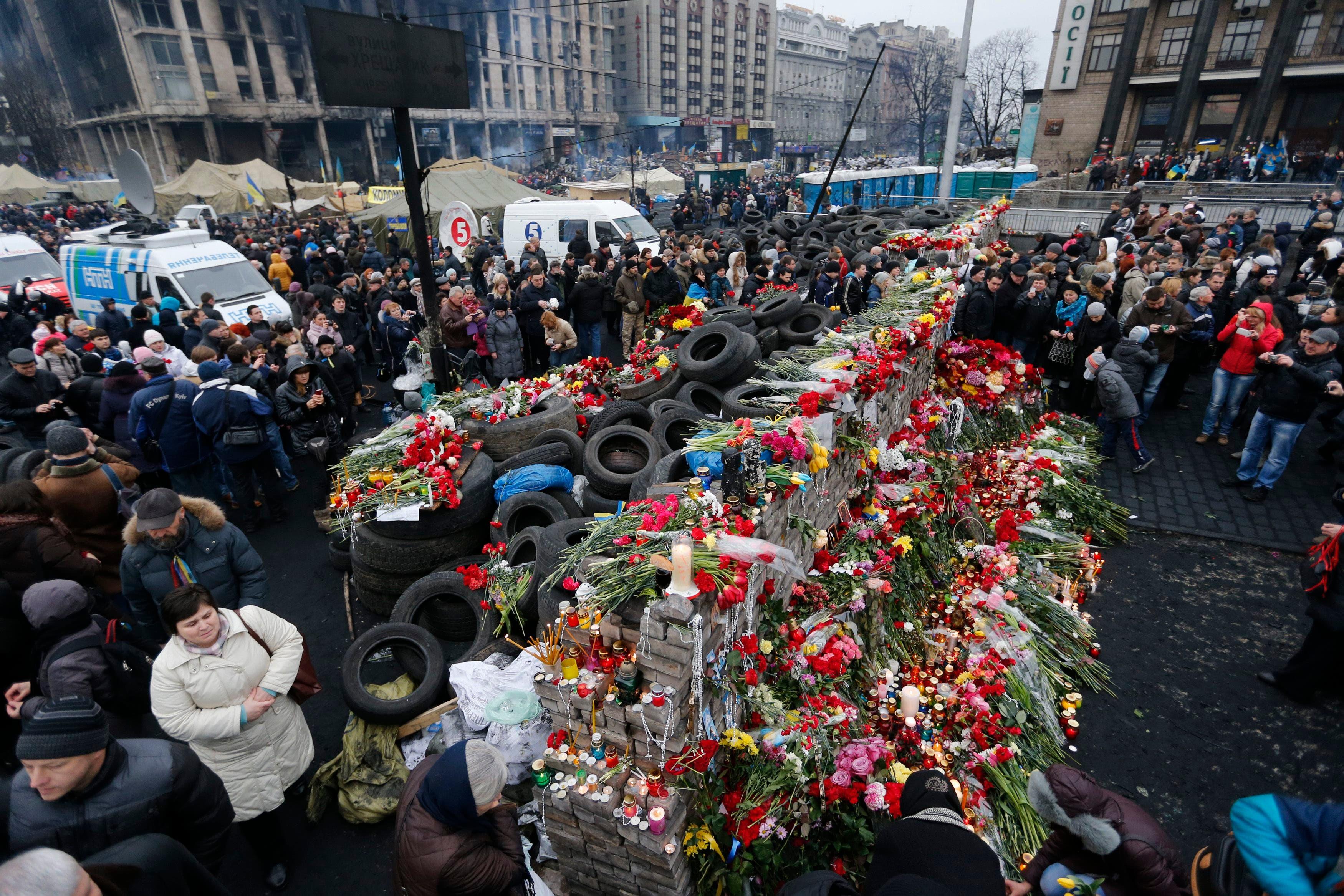 اهالي ضحايا الاشتباكات بين قوات الامن والمعارضين يضعون الورود على نصب تذكاري في ميدان عام في كييف
