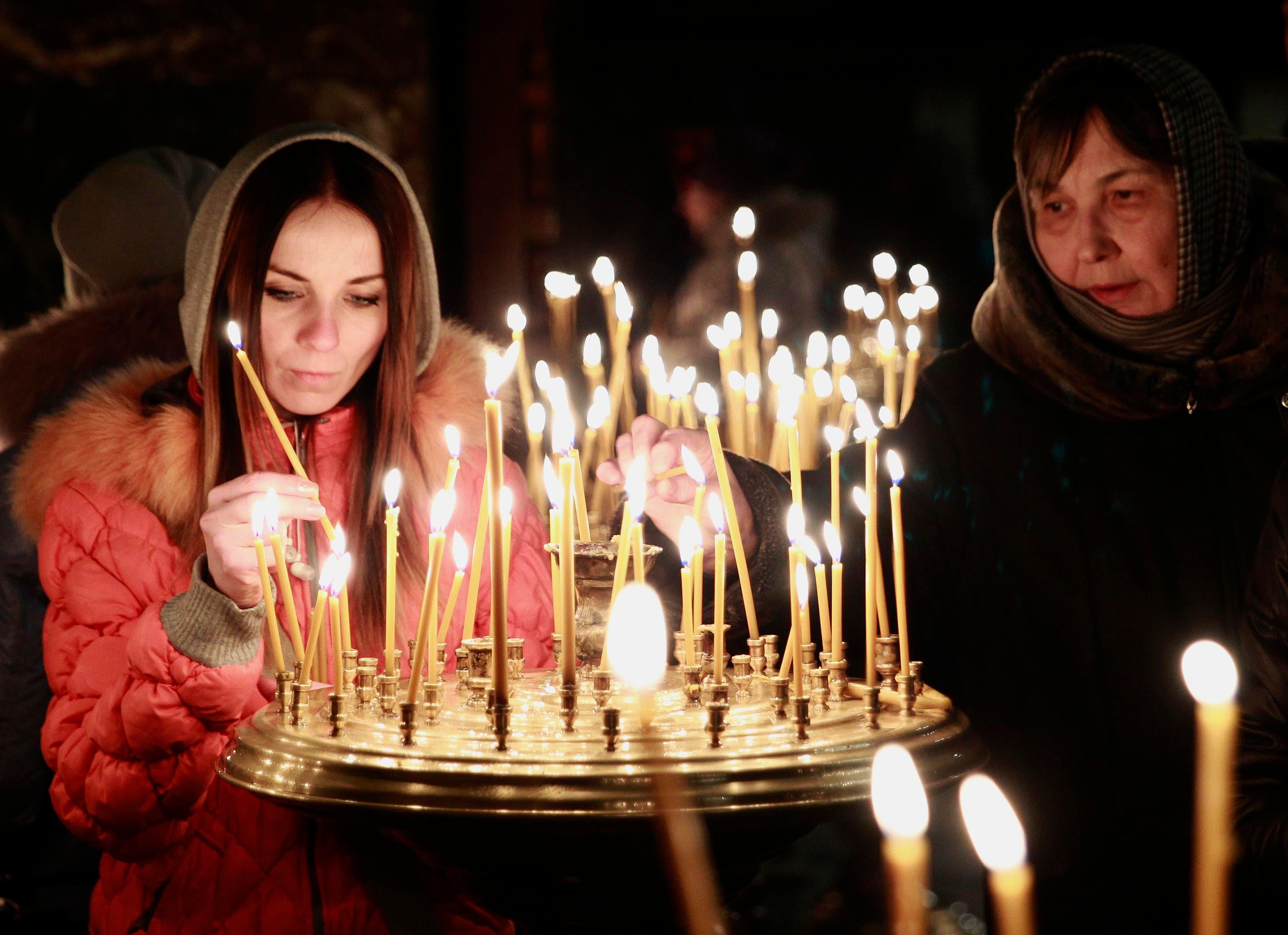 اهالي ضحايا الاشتباكات بين قوات الامن والمعارضين يضيئون الشموع في كنيسة في اوكرانيا
