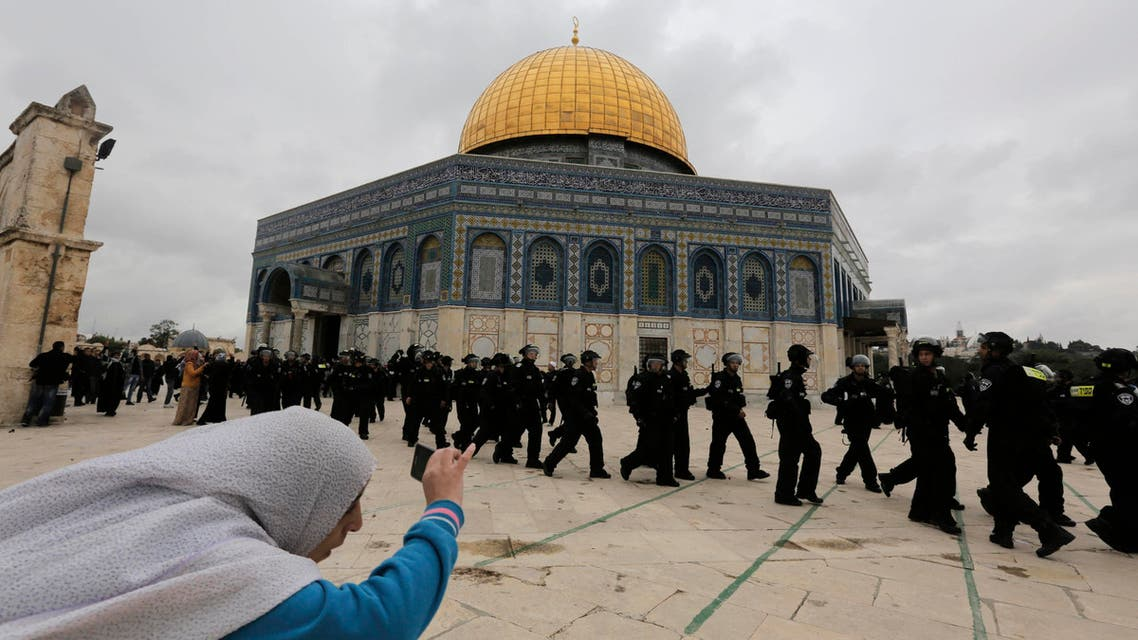 A Palestinian woman takes a picture as Israeli police walk in front of the Dome of the Rock during clashes with stone-throwing protesters. (Reuters)