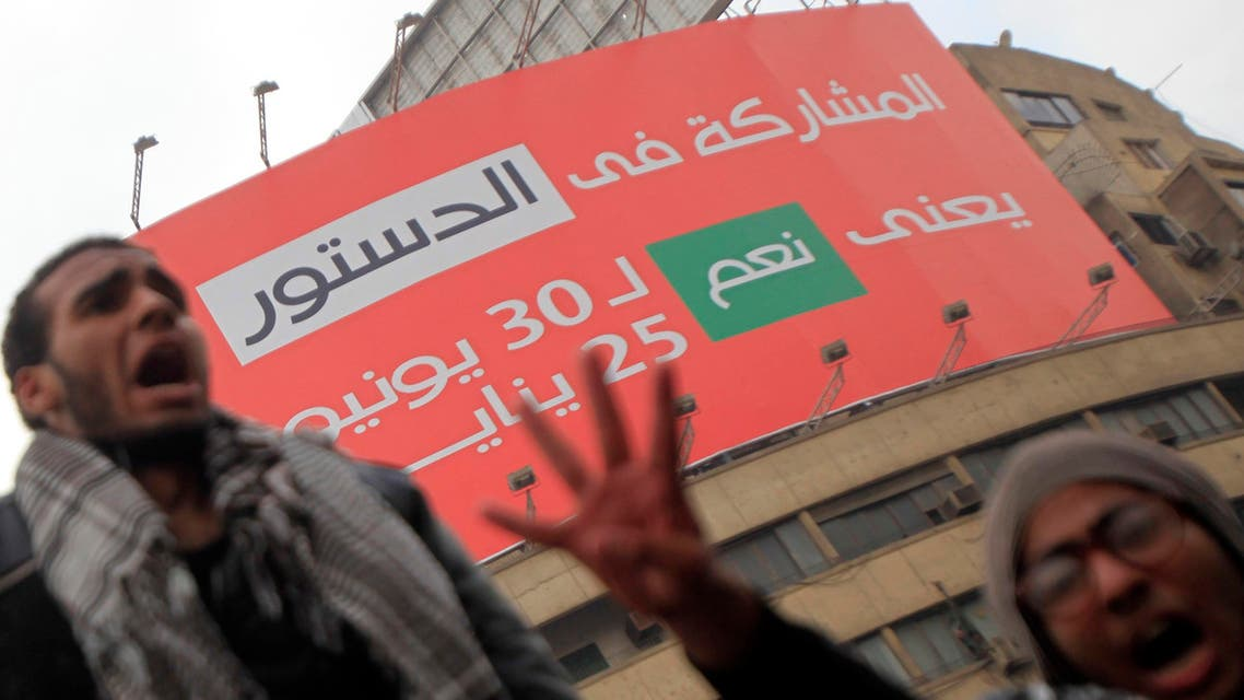 """Pro-Mursi university students and supporters of the Muslim Brotherhood shout slogans in front of a billboard on the new constitution which reads """"Participating in the constitution means 'Yes' to June 30 and January 25"""" at Tahrir Square in Cairo December 1, 2013. reuters"""