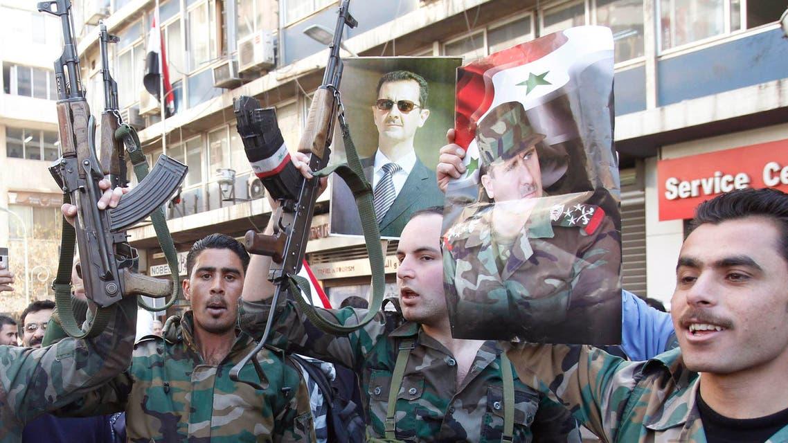 عناصر من جيش النظام ترفع صورة الاسد