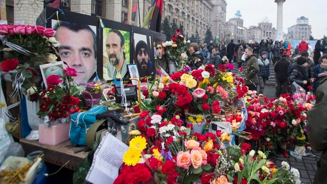 People place flowers at a makeshift memorial as they gather to commemorate the victims of the recent clashes in central Kiev February 23, 2014