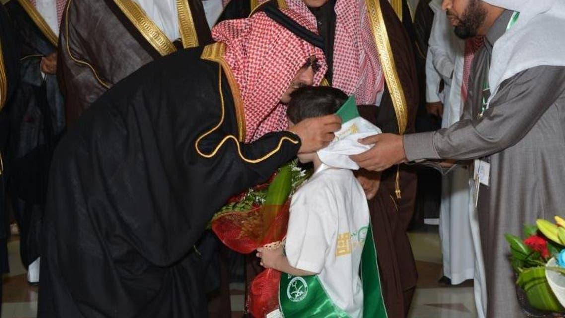 الأمير محمد بن نايف يقبل رأس طفل قدم له الورد