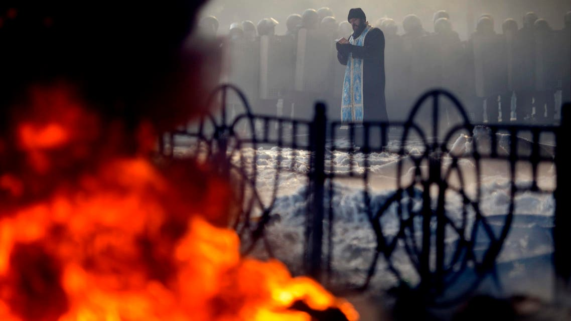 A priest prays in front of riot police during clashes with anti-government protesters in Kiev January 25, 2014. reuters
